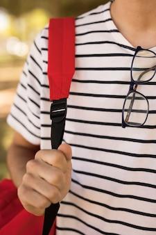 Studente adolescente con gli occhiali che trasportano zaino