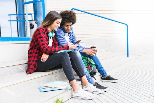 Studente adolescente delle coppie che si siede sulla scala bianca facendo uso del telefono cellulare