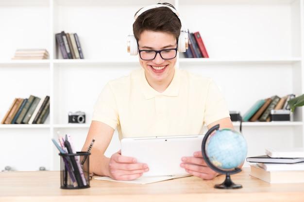 Studente adolescente in occhiali seduto al tavolo e divertirsi con tavoletta