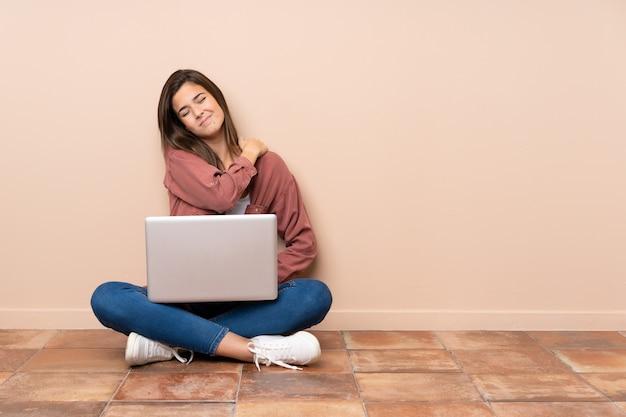 Studente adolescente seduto sul pavimento con un computer portatile che soffrono di dolore alla spalla per aver fatto uno sforzo