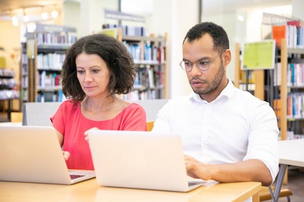 Studente adulto che tradisce durante la prova in biblioteca