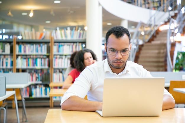 Studente adulto maschio messo a fuoco che effettua ricerca in biblioteca