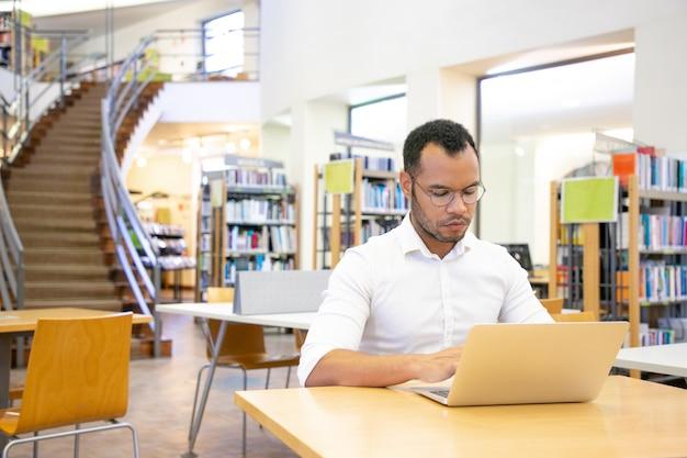 Studente adulto serio che effettua ricerca in biblioteca