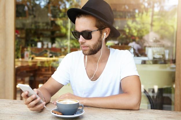 Studente alla moda che indossa occhiali da sole e cappello nero ascoltando le tracce preferite sugli auricolari, utilizzando l'app di musica online sul suo telefono cellulare