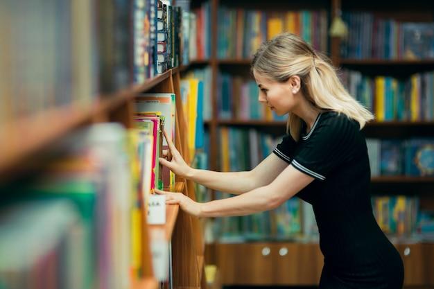 Studente alla ricerca di libri in una biblioteca