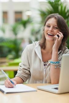 Studente allegro che fa i compiti mentre sulla chiamata dal computer portatile al caffè
