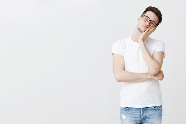 Studente annoiato con gli occhiali si appoggia su una mano e sembra riluttante