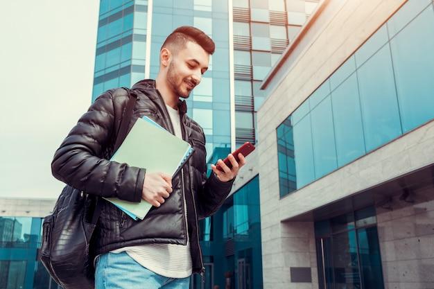 Studente arabo che utilizza smartphone all'esterno. il ragazzo felice esamina il telefono davanti all'edificio moderno dopo le lezioni