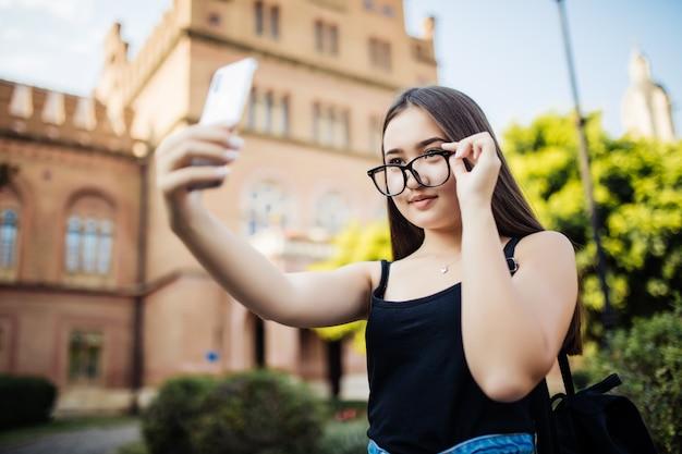 Studente asiatico che prende selfie nel campus