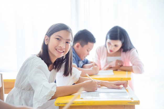 Studente asiatico felice della scuola elementare che studia nell'aula e che sorride alla macchina fotografica.