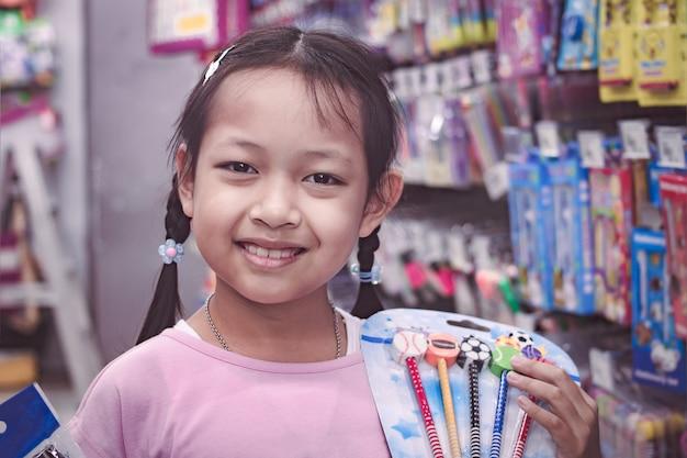 Studente asiatico in negozio di cancelleria comprando penne con sorriso e felice. torna al concetto di scuola