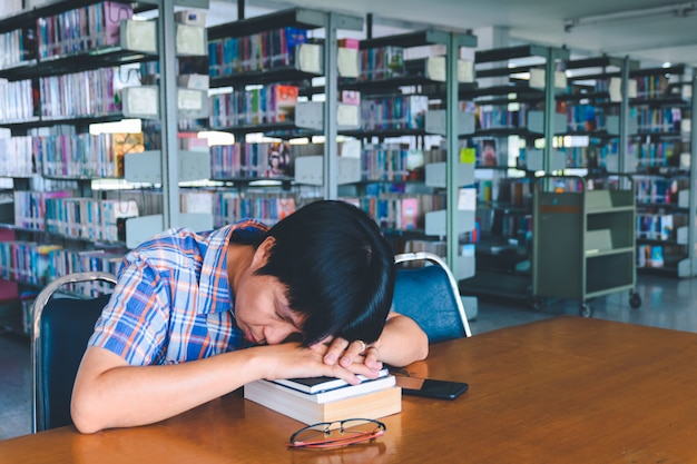 Studente asiatico stanco che dorme allo scrittorio in una biblioteca