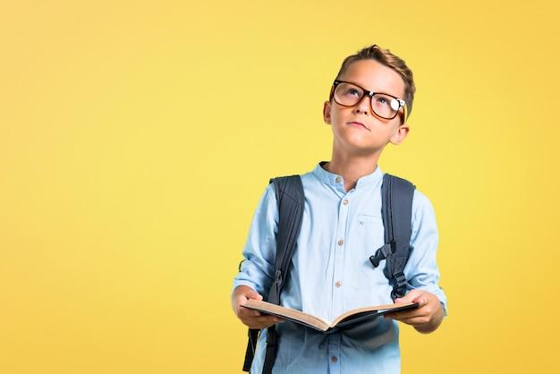 Studente bambino con zaino e occhiali in possesso di un libro su sfondo giallo. di nuovo a scuola