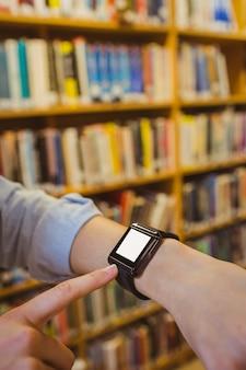 Studente bruna con il suo orologio intelligente in biblioteca