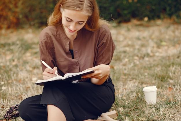 Studente carino che lavora in un parco e utilizza il notebook