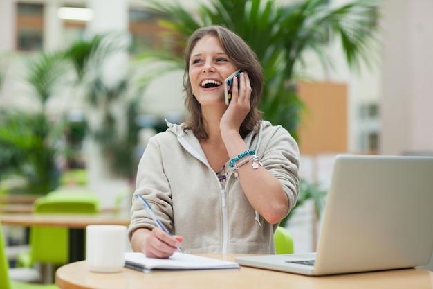 Studente che fa i compiti mentre sulla chiamata dal computer portatile in caffè