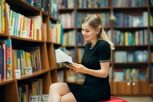 Studente che legge un libro in biblioteca