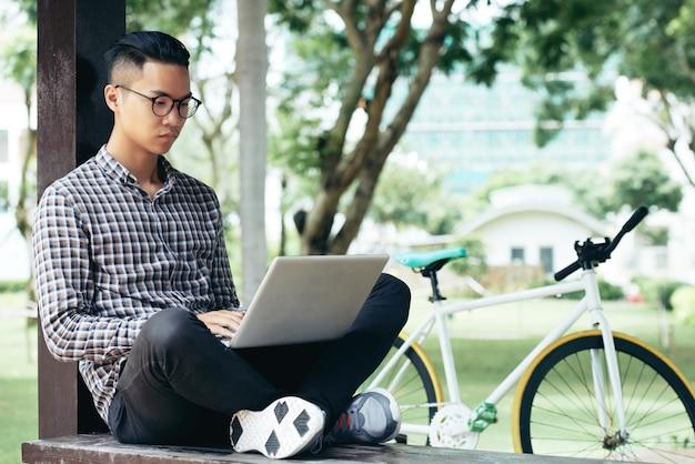 Studente che per mezzo del computer portatile all'aperto