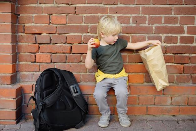 Studente con grande zaino e borsa da lanch si sedette a mangiare il suo lanch vicino all'edificio scolastico.
