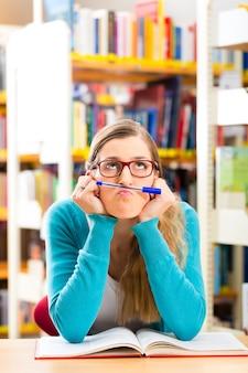 Studente con libri di apprendimento in biblioteca
