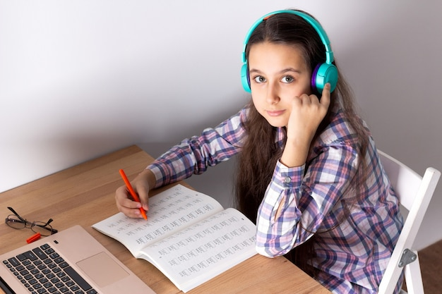 Studente con un computer portatile che ascolta un webinar online con le cuffie. concetto di e-learning.