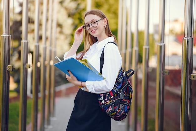 Studente con uno zaino in un cortile della scuola