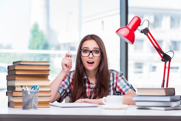 Studente della giovane donna che prepara per gli esami universitari