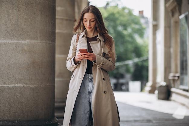 Studente della giovane donna dall'università che parla sul telefono
