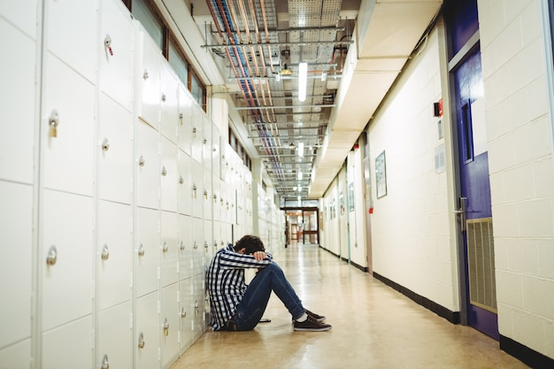 Studente depresso che si siede nello spogliatoio