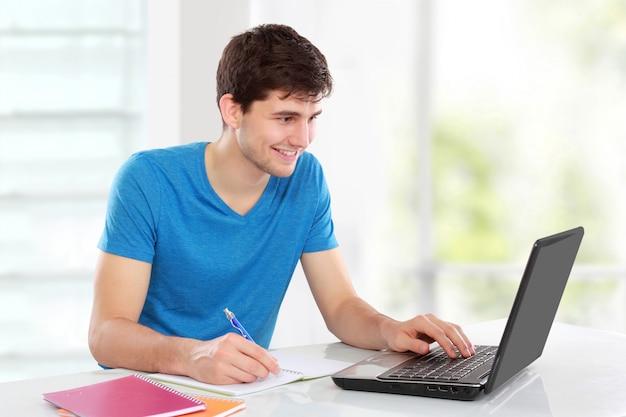 Studente di college che per mezzo del suo computer portatile
