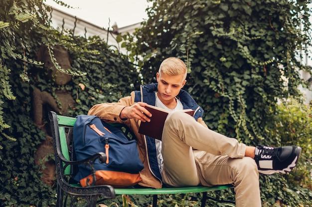 Studente di college con il libro di lettura zaino legge agghiacciante hotel moderno giorno di autunno piovoso