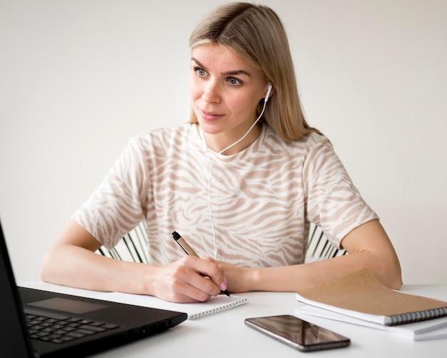Studente di vista frontale seduto alla sua scrivania di casa