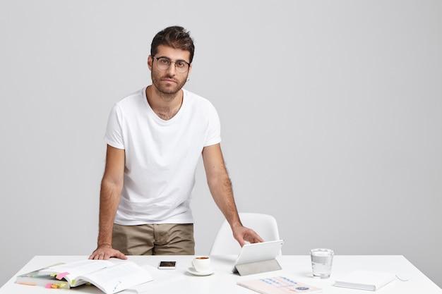 Studente europeo lavora al documento del corso, cerca informazioni nei libri o in internet