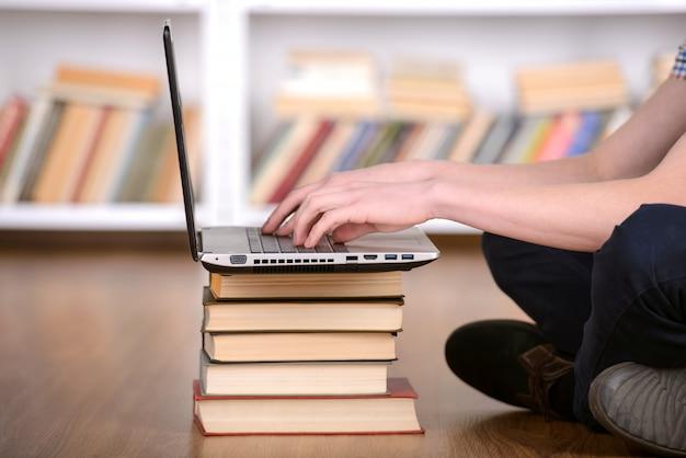 Studente felice che lavora al computer portatile in biblioteca.