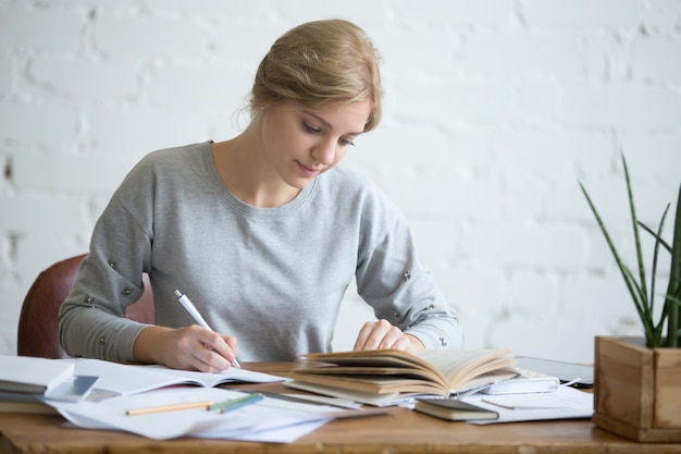 Studente femminile che esegue un compito scritto in un copybook