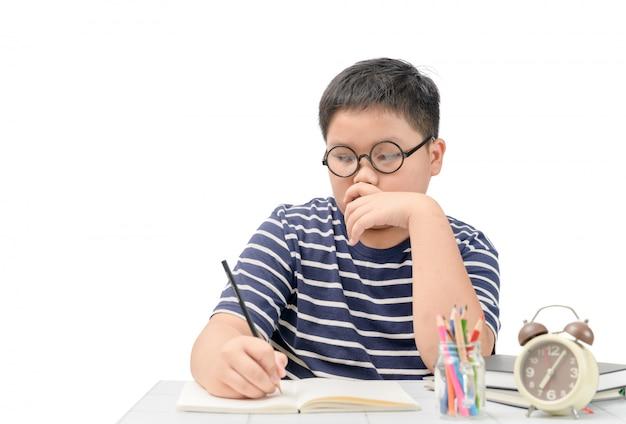 Studente grasso che pensa mentre fa i suoi compiti