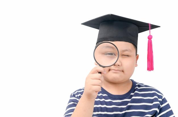 Studente grasso guardando attraverso una lente di ingrandimento