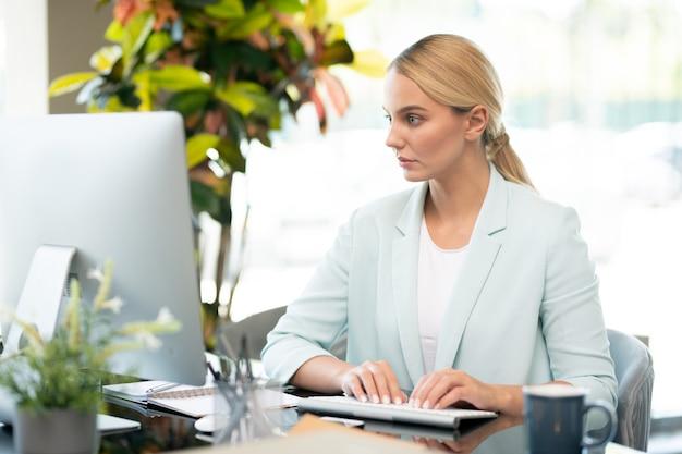 Studente grazioso che si concentra sulla lettura delle informazioni in linea sullo schermo del computer durante la digitazione dalla scrivania