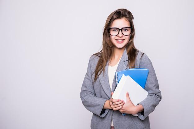Studente grazioso e giovane con i grandi vetri vicino ad alcuni libri che sorridono sul fondo bianco