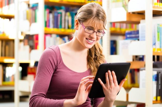 Studente in biblioteca che impara con il computer tablet