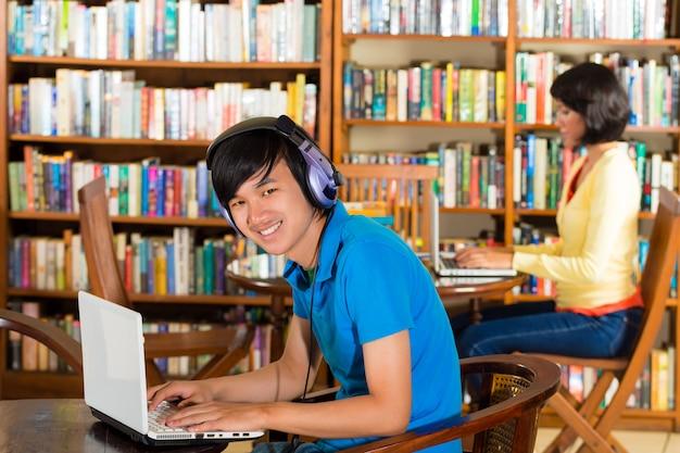 Studente in biblioteca con il computer portatile