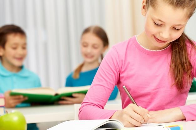 Studente in possesso di una matita con sfondo sfocato compagni di classe