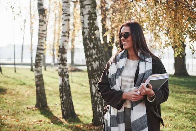 Studente intelligente in una passeggiata. il giovane castana sorridente in occhiali da sole sta nel parco vicino agli alberi e tiene il blocco note