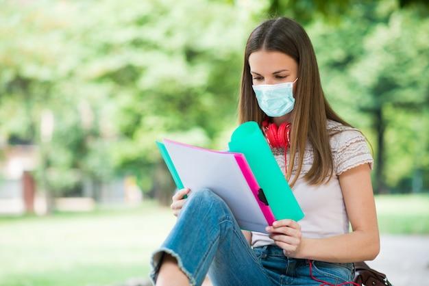 Studente mascherato che studia in un parco di fronte alla scuola