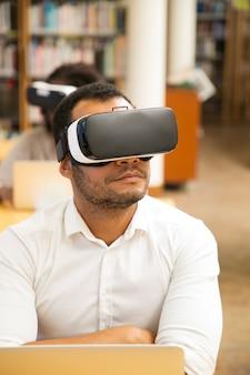 Studente maschio adulto che utilizza gli occhiali vr per il lavoro durante le lezioni