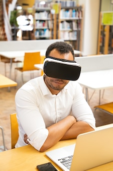 Studente maschio che indossa i vetri di vr che lavorano al computer portatile