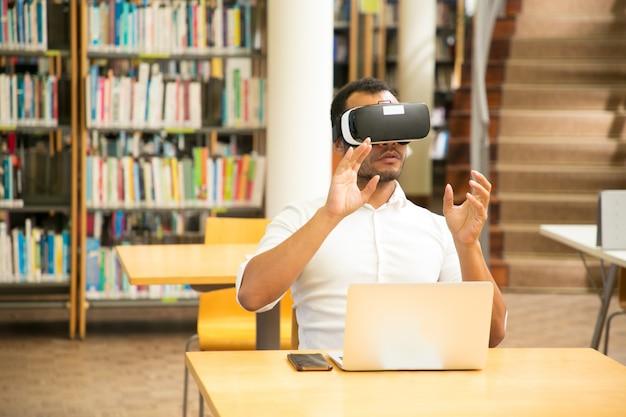 Studente maschio che lavora con il simulatore vr in biblioteca