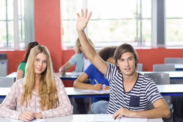 Studente maschio che solleva mano in aula