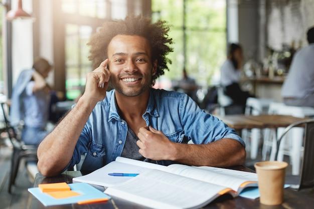 Studente maschio dalla carnagione scura adorabile hipster con acconciatura afro che si siede nella caffetteria circondato da libri e quaderni con un sorriso felice mentre parla al telefono