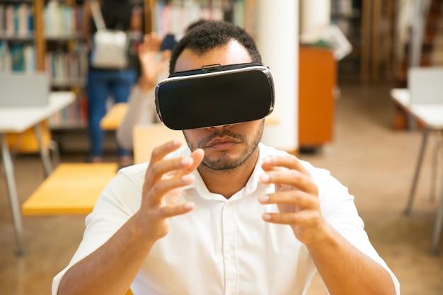 Studente maschio emozionante che utilizza il simulatore di vr durante la lezione